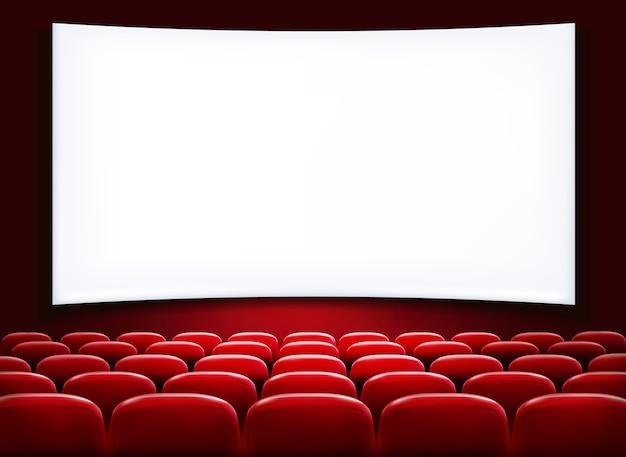 File di sedili rossi del cinema o del teatro davanti allo schermo vuoto bianco.