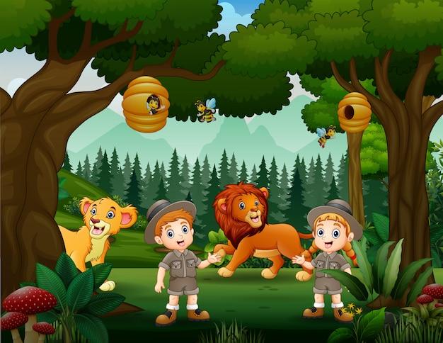 Ragazzo e ragazza di safari nella foresta con i leoni