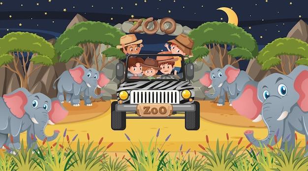 Safari di notte con molti bambini che guardano il gruppo di elefanti