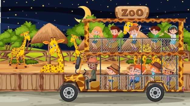 Safari di notte con molti bambini che guardano un gruppo di giraffe