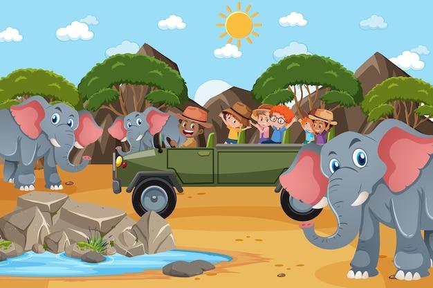 Scena del safari con bambini su un'auto turistica che guardano un gruppo di elefanti