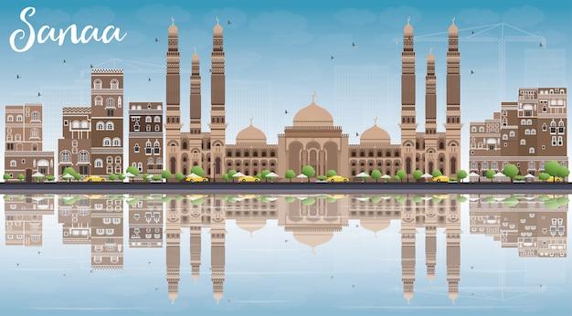 Skyline di sanaa (yemen) con edifici marroni, cielo blu e riflessi.