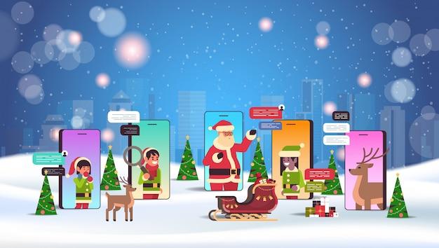 Il babbo natale con gli aiutanti degli elfi che usando concetto di celebrazione di feste di natale di comunicazione del nuovo anno di comunicazione della rete sociale di app
