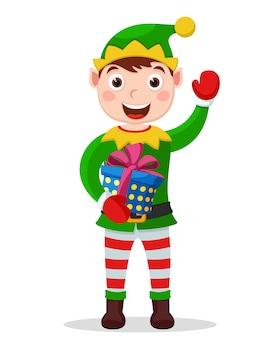 L'assistente di babbo natale tiene una confezione regalo e le onde della mano su uno sfondo bianco. carattere natalizio
