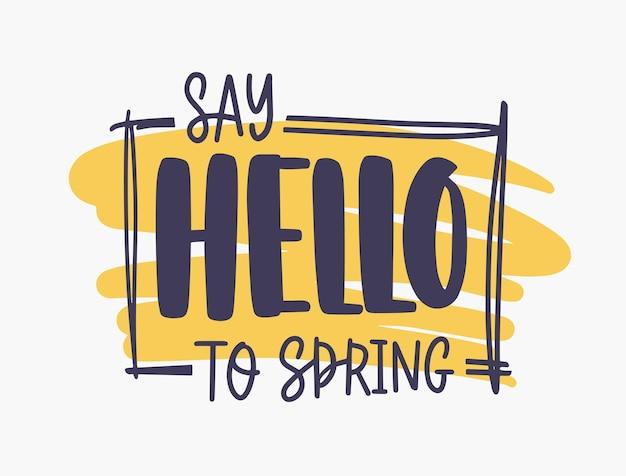 Dire hello to spring frase ispiratrice scritta con carattere elegante o script all'interno di una cornice rettangolare su macchia di vernice arancione isolata su bianco