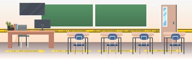 Aula scolastica con cartelli adesivi gialli di allontanamento sociale misure di protezione dall'epidemia di coronavirus
