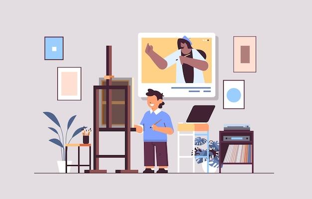 Scolaro con insegnante donna artista nella finestra del browser web che dipinge l'immagine durante la videochiamata autoisolamento
