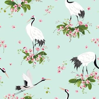 Modello senza cuciture con gru giapponesi e fiori di orchidea tropicale, sfondo di uccelli retrò, stampa di moda floreale, set di decorazioni giapponesi di compleanno. illustrazione vettoriale