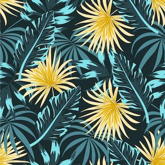 Modello tropicale senza cuciture con piante gialle e blu