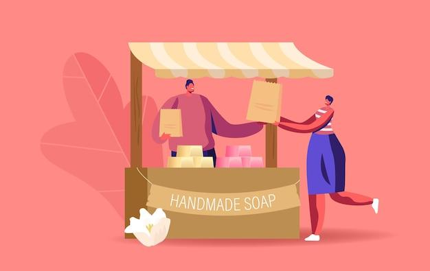 Personaggio maschile venditore stand presso una bancarella di legno che presenta sapone fatto a mano sul mercato dell'artigianato