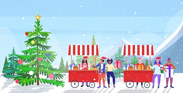 Venditori in cappello di babbo natale che vendono scatole presenti mescolano gente di razza che fa shopping e compra regali al mercatino di natale o alle vacanze invernali