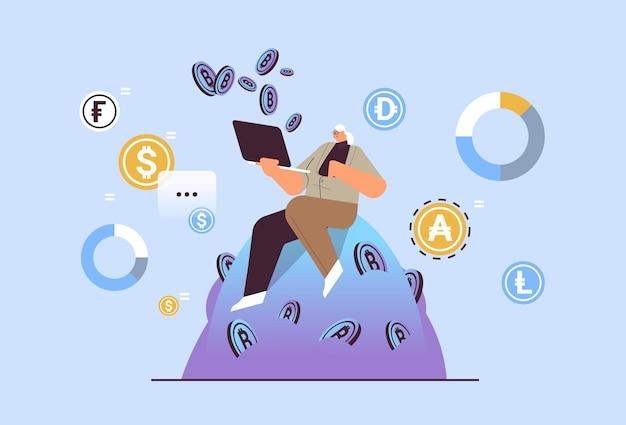 Donna d'affari senior che acquista o vende bitcoin su laptop online trasferimento di denaro pagamento internet blockchain criptovaluta