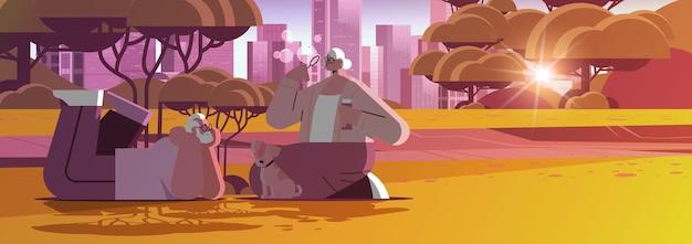 Coppia senior che soffia bolle e trascorre del tempo con un cagnolino nel concetto di pensione relax del parco urbano