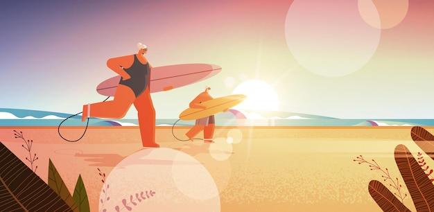 Coppia senior con tavole da surf uomo di età donna surfisti che tengono tavole da surf vacanze estive concetto di vecchiaia attiva