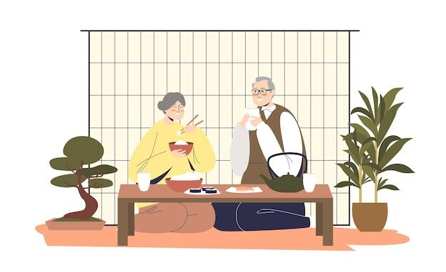 Coppia giapponese senior cenando insieme a casa seduta isolata
