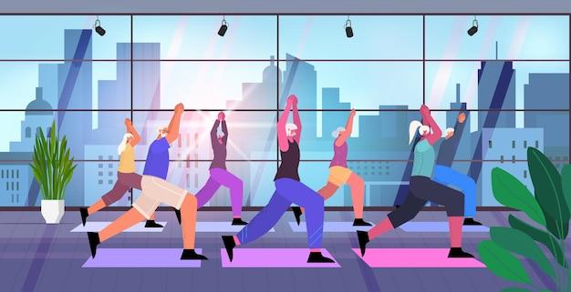 Gruppo di persone anziane che fanno squat uomini anziani donne che si allenano in palestra allenamento aerobico stile di vita sano vecchiaia attiva