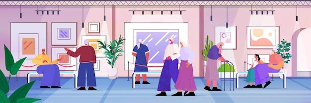 Persone anziane che visitano la galleria d'arte uomini anziani donne visitatori che guardano mostre nel museo concetto di vecchiaia illustrazione vettoriale a figura intera orizzontale