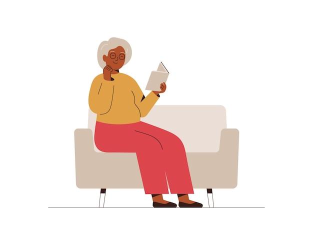 La donna anziana si siede sul divano e legge il libro la nonna trascorre del tempo a casa con un libro