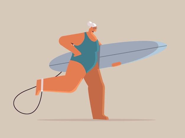 Donna anziana con tavola da surf surfista femmina invecchiata che tiene tavola da surf vacanze estive attiva vecchiaia concept