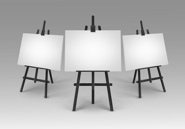 Set di cavalletti in legno nero con mock up tele vuote vuote isolate su priorità bassa