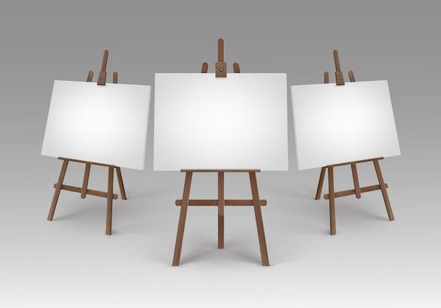 Set di cavalletti in legno marrone con mock up tele vuote vuote isolate su priorità bassa