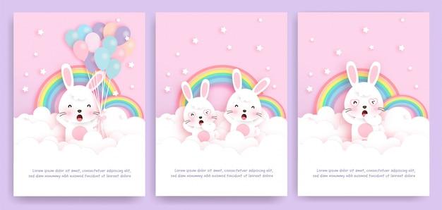 Set di carte con simpatici conigli in piedi sul cloud.