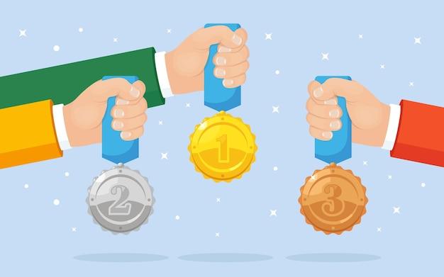 Set di medaglia d'oro, d'argento, di bronzo con la stella per il primo posto in mano. realizzazione, concetto di vittoria