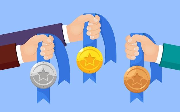 Set di medaglia d'oro, d'argento, di bronzo con la stella per il primo posto in mano.