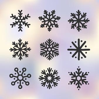 Set di icone di fiocchi di neve scarabocchi disegnati a mano sullo sfondo sfumato del cielo invernale simbolo di inverno del nuovo anno