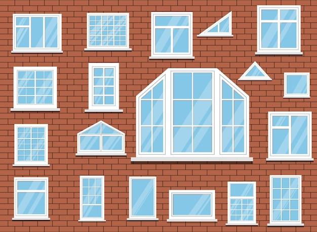 Insieme delle finestre di plastica bianche isolate sulla priorità bassa del muro di mattoni rossi.