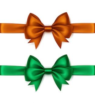 Set di fiocchi di raso verde smeraldo arancione lucido e nastri vista dall'alto close up isolati su sfondo bianco
