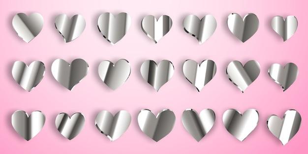 Set di cuori d'argento lucido con ombre su sfondo rosa