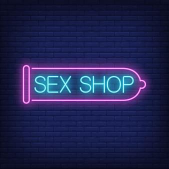 Insegna al neon del sexshop. preservativo rosa sul muro di mattoni. pubblicità luminosa di notte.