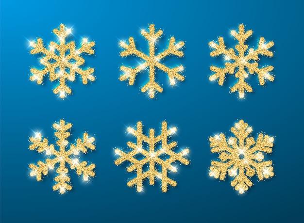 Fiocchi di neve incandescente brillanti glitter oro su sfondo blu. decorazione di natale e capodanno.