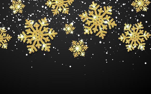 Fiocchi di neve d'oro splendente su sfondo nero