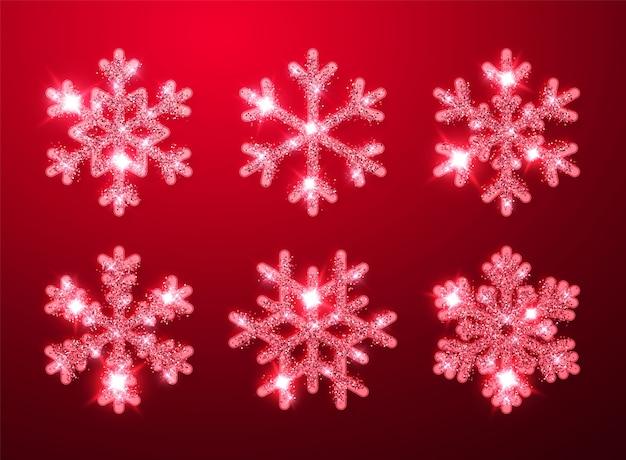Fiocchi di neve incandescente scintillio rosso brillante su sfondo rosso. decorazione di natale e capodanno.