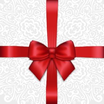 Fiocco di nastro di raso rosso vacanza splendente su sfondo ornamentale di pizzo bianco.