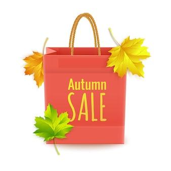 Shopping bag di carta con testo e foglie cadute dietro isolato