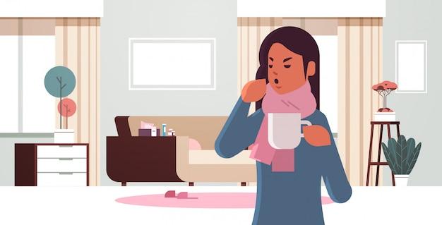 Donna malata che starnutisce bevendo tè caldo