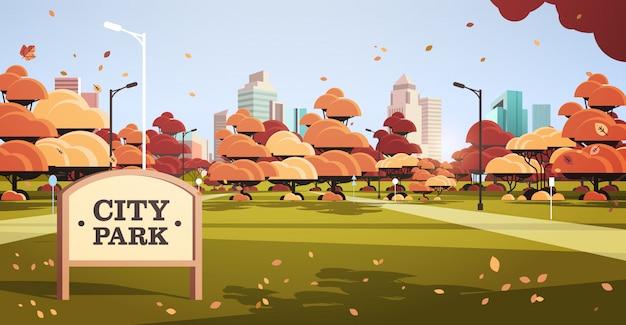 Cartello in autunno skyline del parco cittadino con foglie gialle che cadono al sole edifici skyskraper