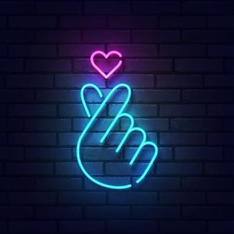 Segno del dito cuore con luci al neon colorate isolato su un muro di mattoni.