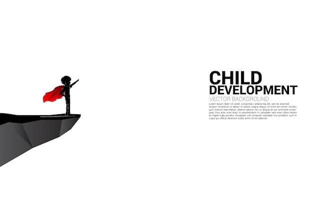 Siluetta del ragazzo nel punto del vestito del supereroe dalla scogliera. concetto di inizio dell'istruzione e futuro dei bambini.