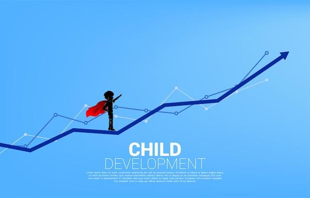 Siluetta del ragazzo in tuta da supereroe in piedi sulla freccia del grafico a linee. concetto di inizio dell'istruzione e futuro dei bambini.
