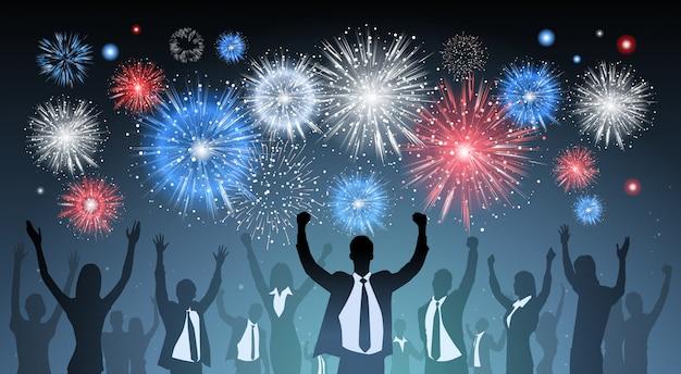 La gente di affari della siluetta raggruppa nell'ambito di scoppi di saluto variopinti dei fuochi d'artificio su fondo blu