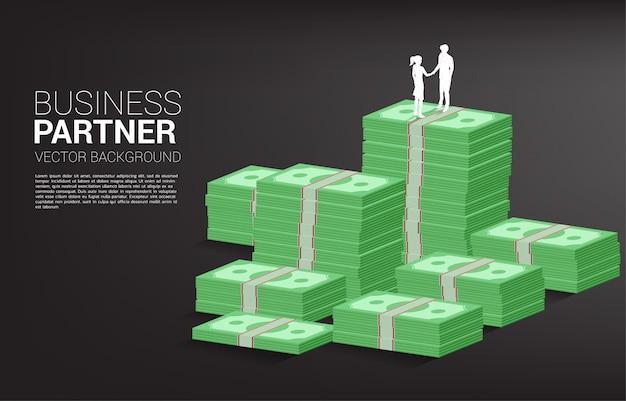 Siluetta della stretta di mano della donna di affari e dell'uomo d'affari sopra la pila della banca. concetto di collaborazione commerciale e cooperazione.
