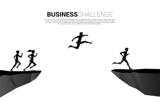 Siluetta dell'uomo d'affari e della donna di affari che salta sopra il divario della valle. concetto di rischio di sfida aziendale.