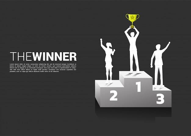 Siluetta dell'uomo d'affari e della donna di affari con il trofeo del campione sul podio.