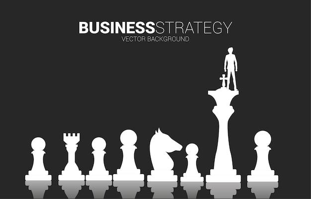 Siluetta dell'uomo d'affari sul re del pezzo degli scacchi. concetto di business di pianificazione strategica e successo
