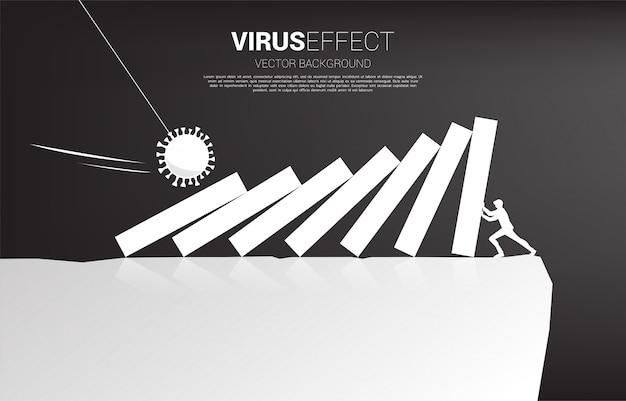 Siluetta dell'uomo d'affari che cade dall'effetto domino dal virus della corona per cadere dalla valle. concetto di crisi economica dovuta allo scoppio del virus.