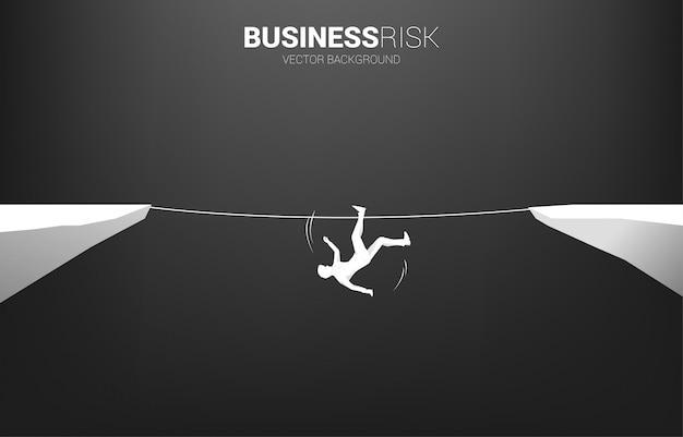 Siluetta dell'uomo d'affari che cade dal modo della passeggiata della corda.